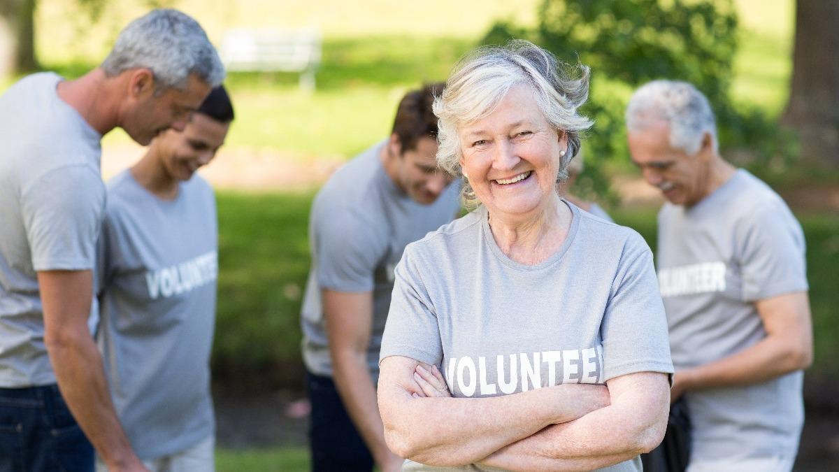 small group of smiling retirees volunteering outside wearing grey volunteer shirts.