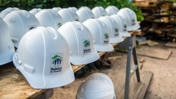 white hard hats on a construction site with twin cities habitat for humanity logos