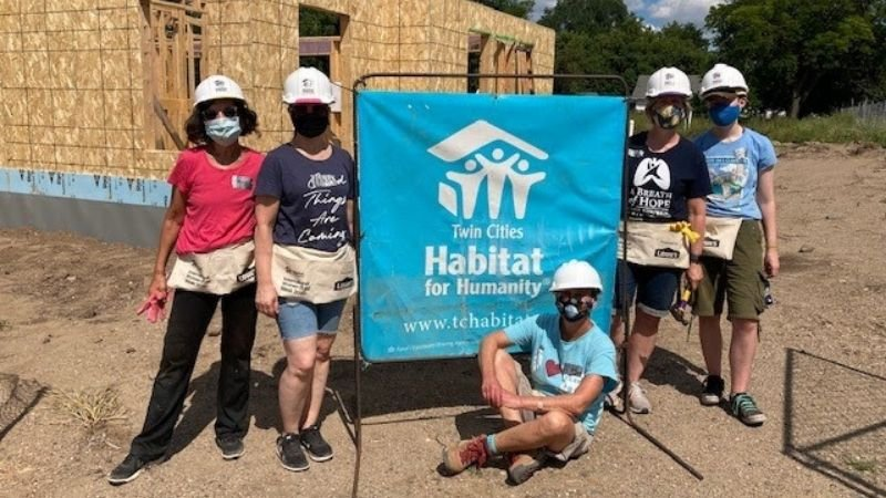 A group of volunteers sitting around a Habitat for Humanity banner.