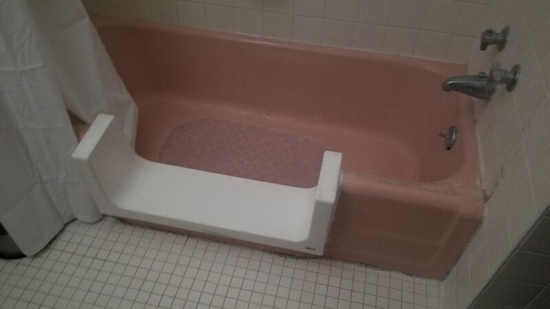 White tile in a bathroom, surrounding a pink bathtub. The middle of the side of the tub has been cut out, and replaced with a u-shaped white piece so you can step into the tub.