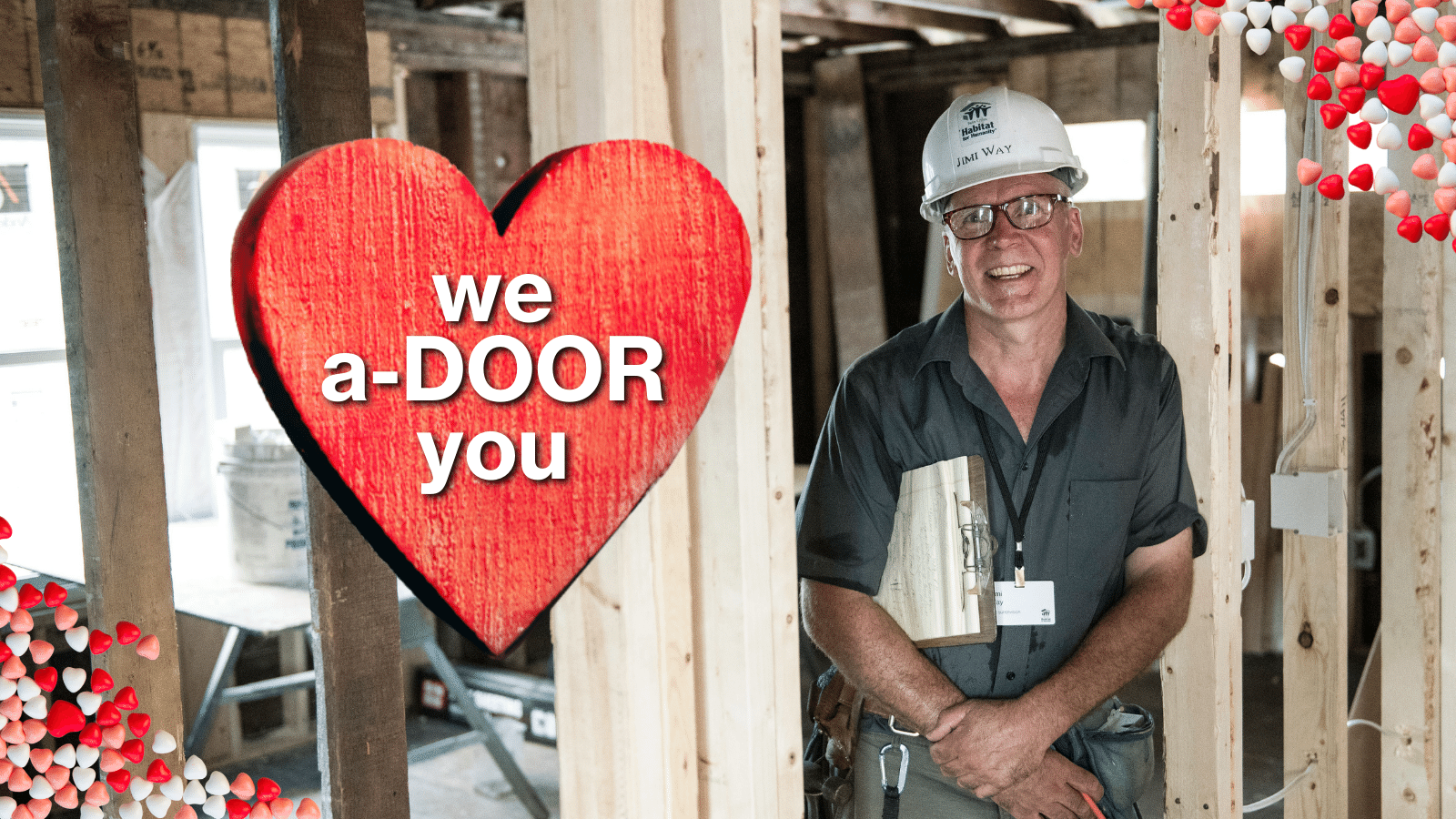 """Site Supervisor Jimi stands in a doorway under construction with text """"We a-DOOR you."""""""
