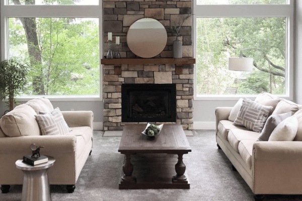 photo of a staged living room with two couches, a coffee table, in front of a fireplace