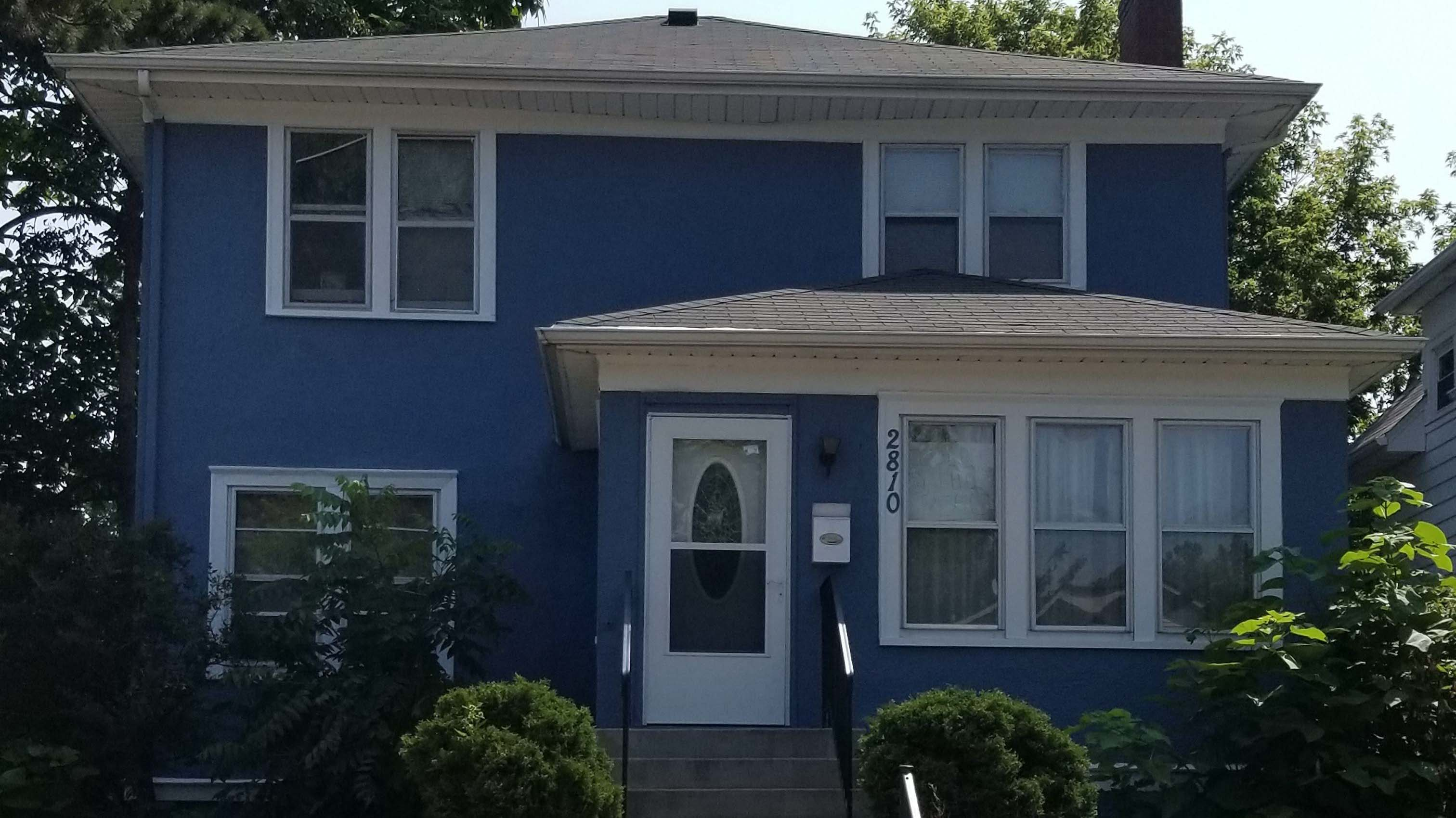 A blue house with a new railing in the front.