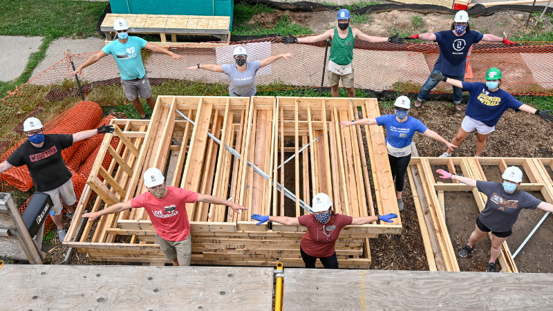 A group of socially-distanced people at a Habitat build site standing with their arms out