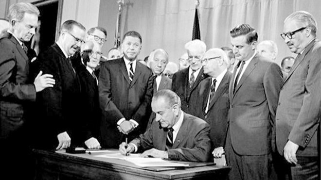 President Johnson signing Fair Housing Act in 1968- Walter Mondale looks (above to the right)
