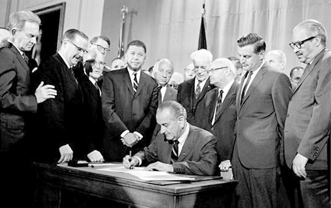 President Johnson signing Fair Housing Act in 1968. Walter Mondale looks (above to the right)