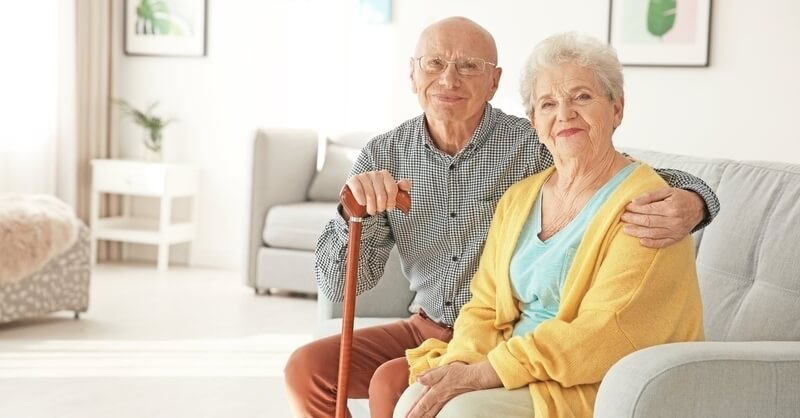Elderly couple sitting together, male has his arm around female