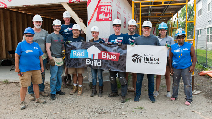 State legislators and Habitat staff holding a sign that says Red Blue Build.