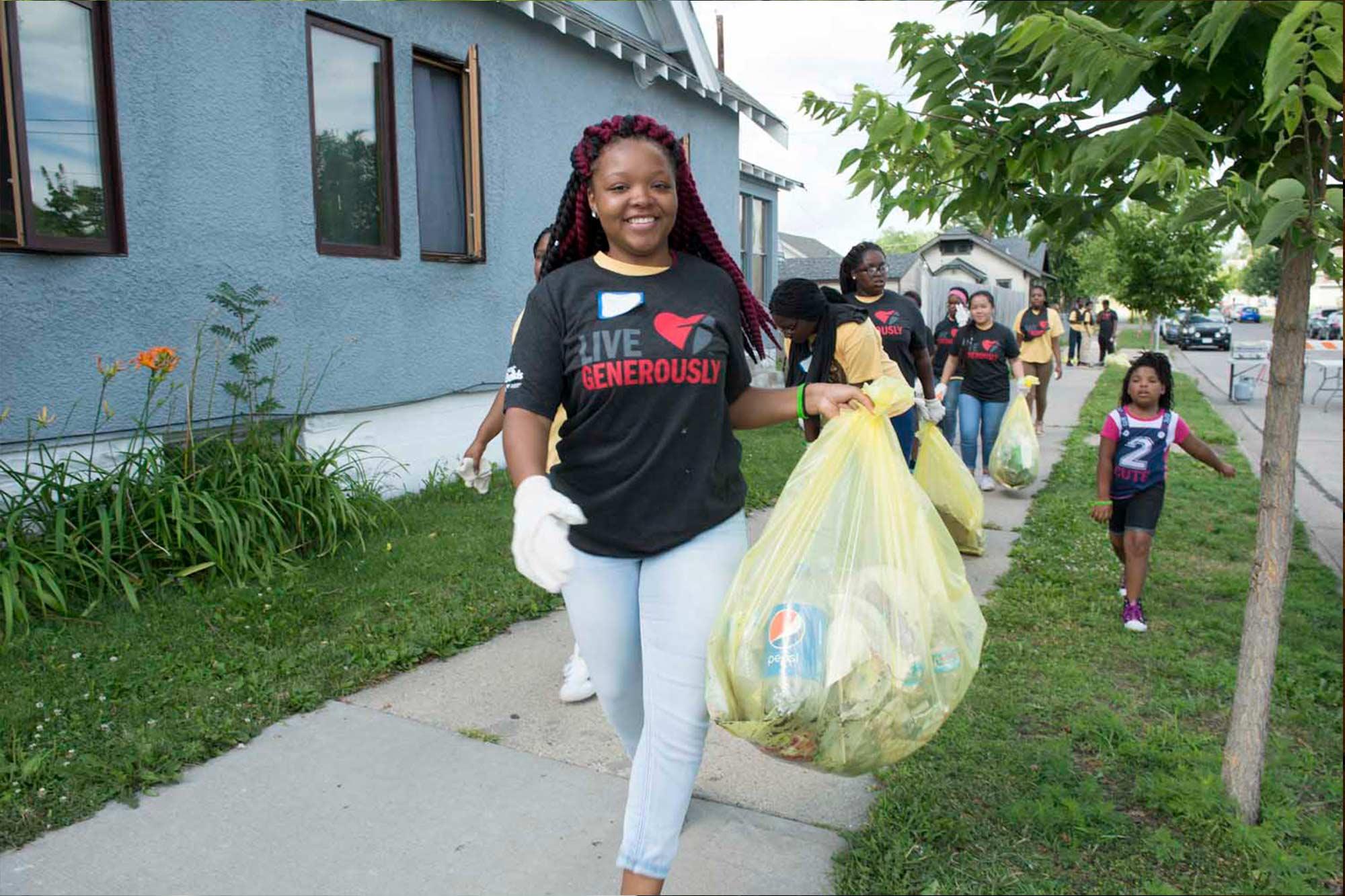 Jordan week of kindness participant carrying a bag of trash