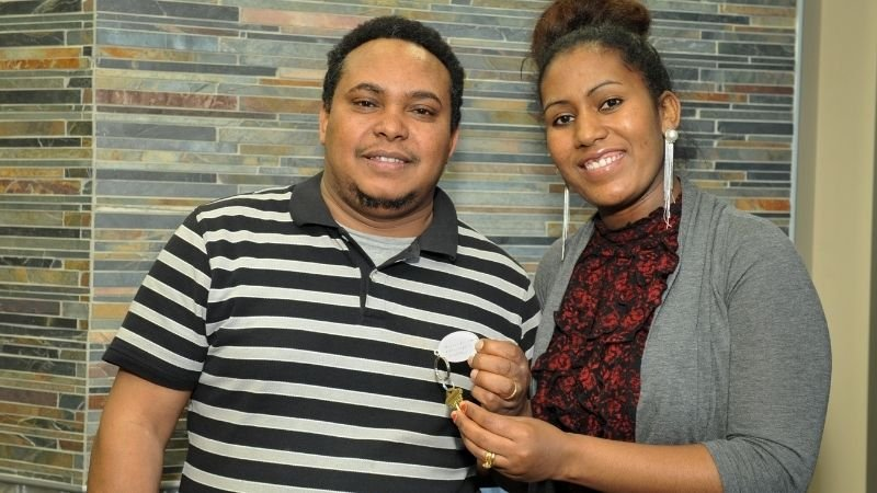 Two Habitat homeowners holding the keys to their new home.