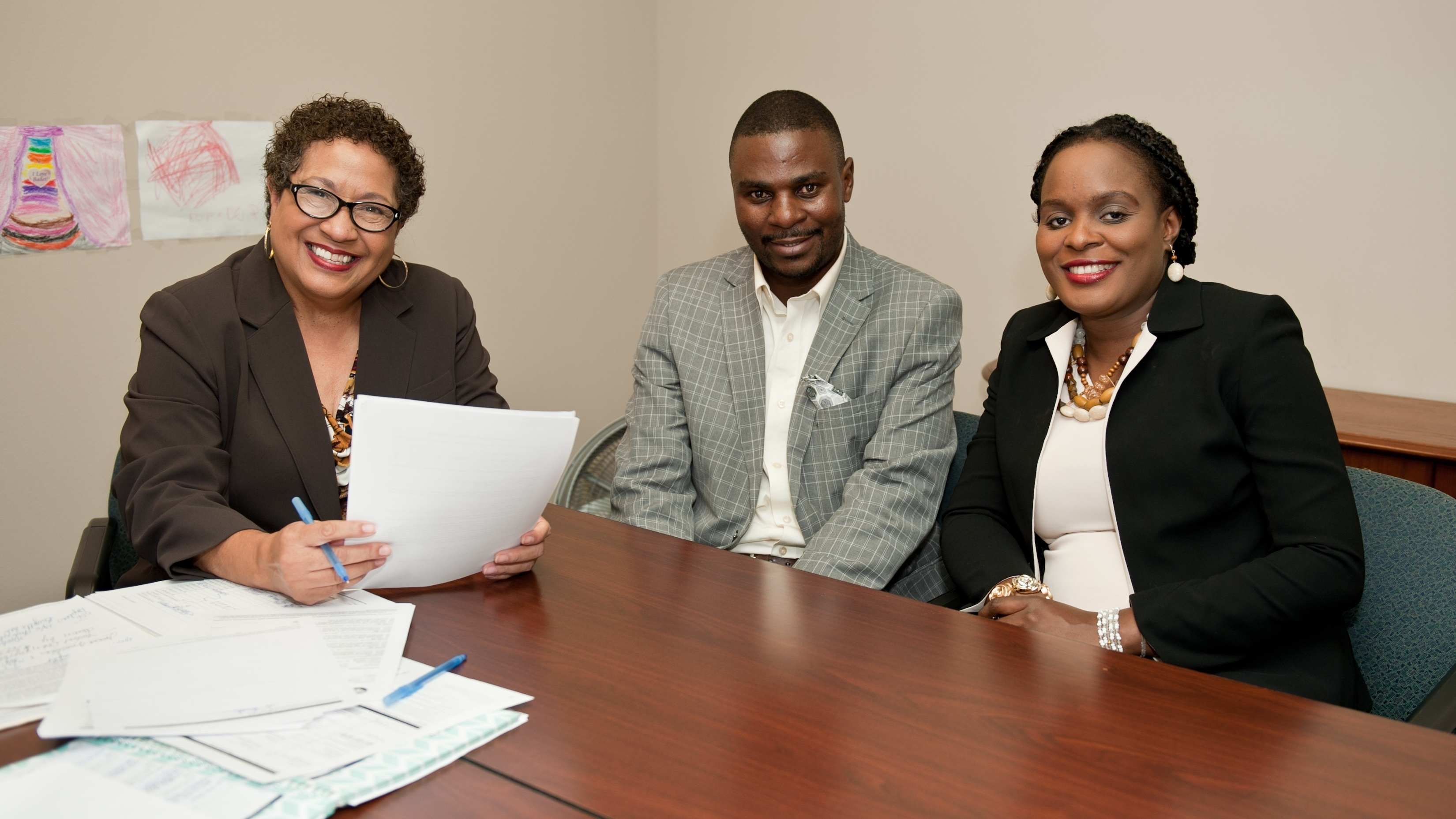 Linda, Financial Coach at Model Cities, smiles with Fred and Brigitte at a coaching session.