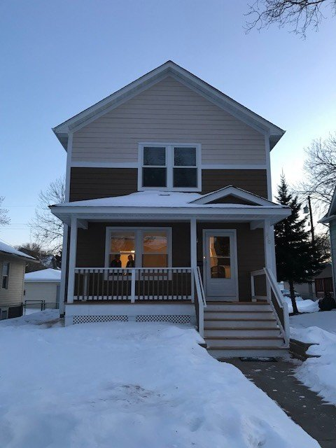 With a clear sky in the snow, a two-story Habitat house with peach siding at the top near the roof, and brown siding on the bottom half of the house. A short set of stairs leads up to the covered porch and front door. The house has a pitched roof and white trim.