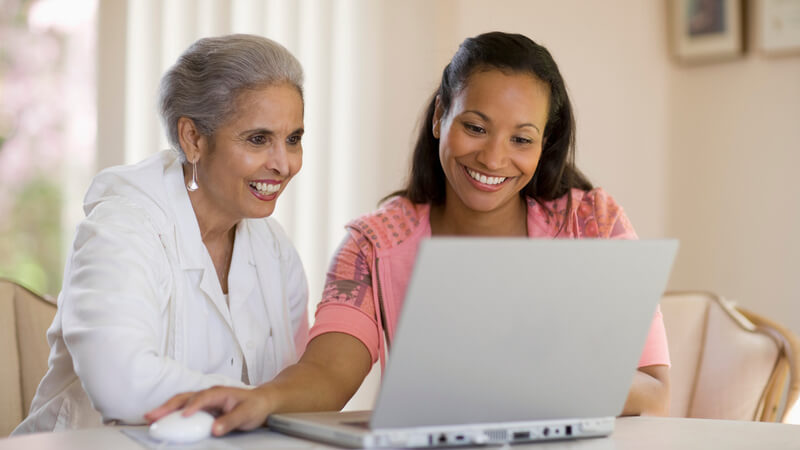 A mother and daughter smiling and sitting at a table looking at a laptop.