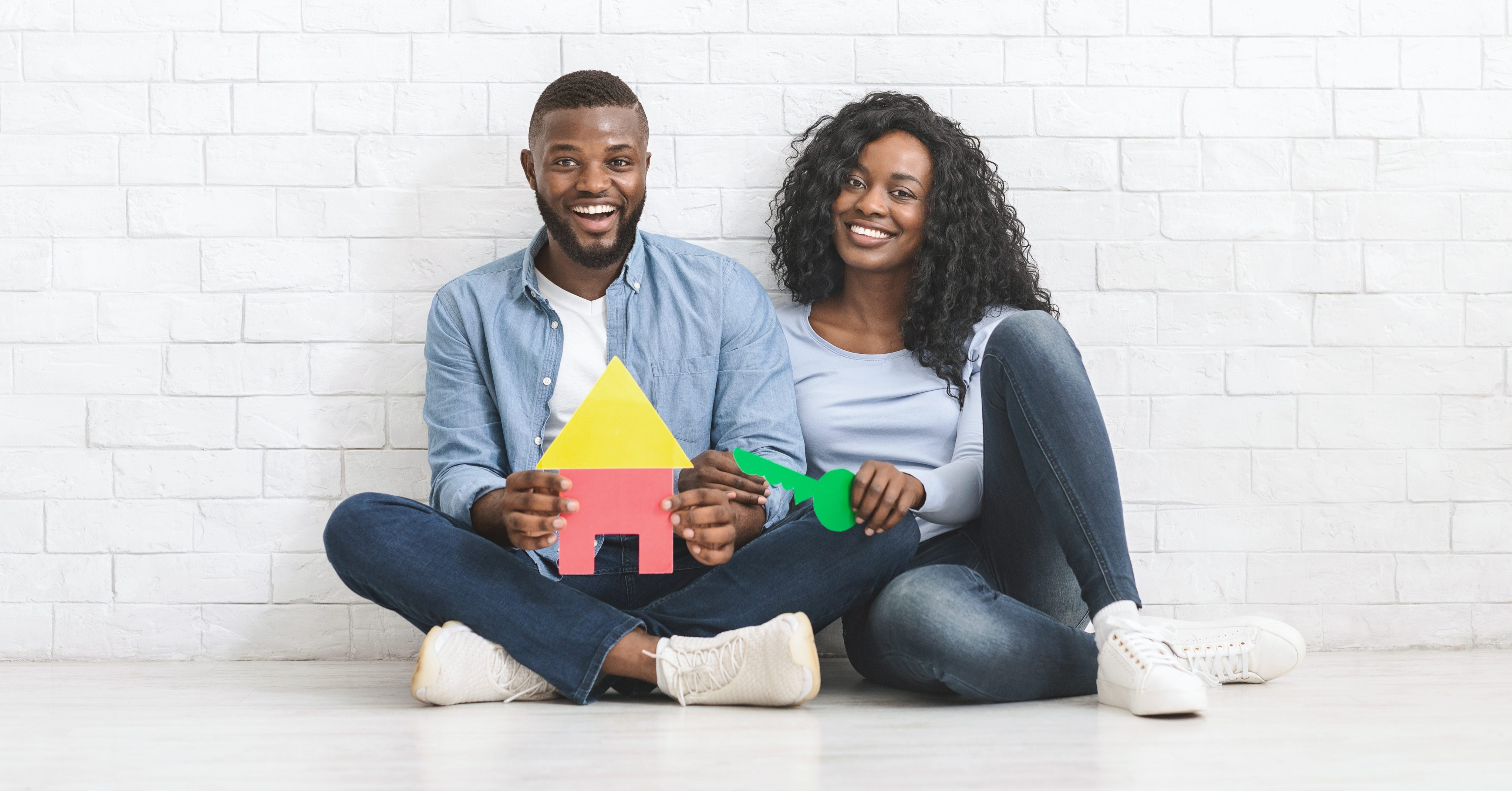Young black home buyer couple holding papercraft home and key.