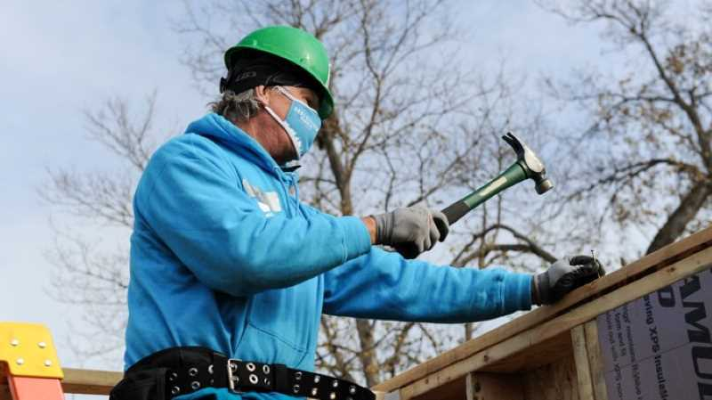 Chris coleman swinging a hammer outside a Habitat house in a blue sweatshirt, green hard hat, and face mask