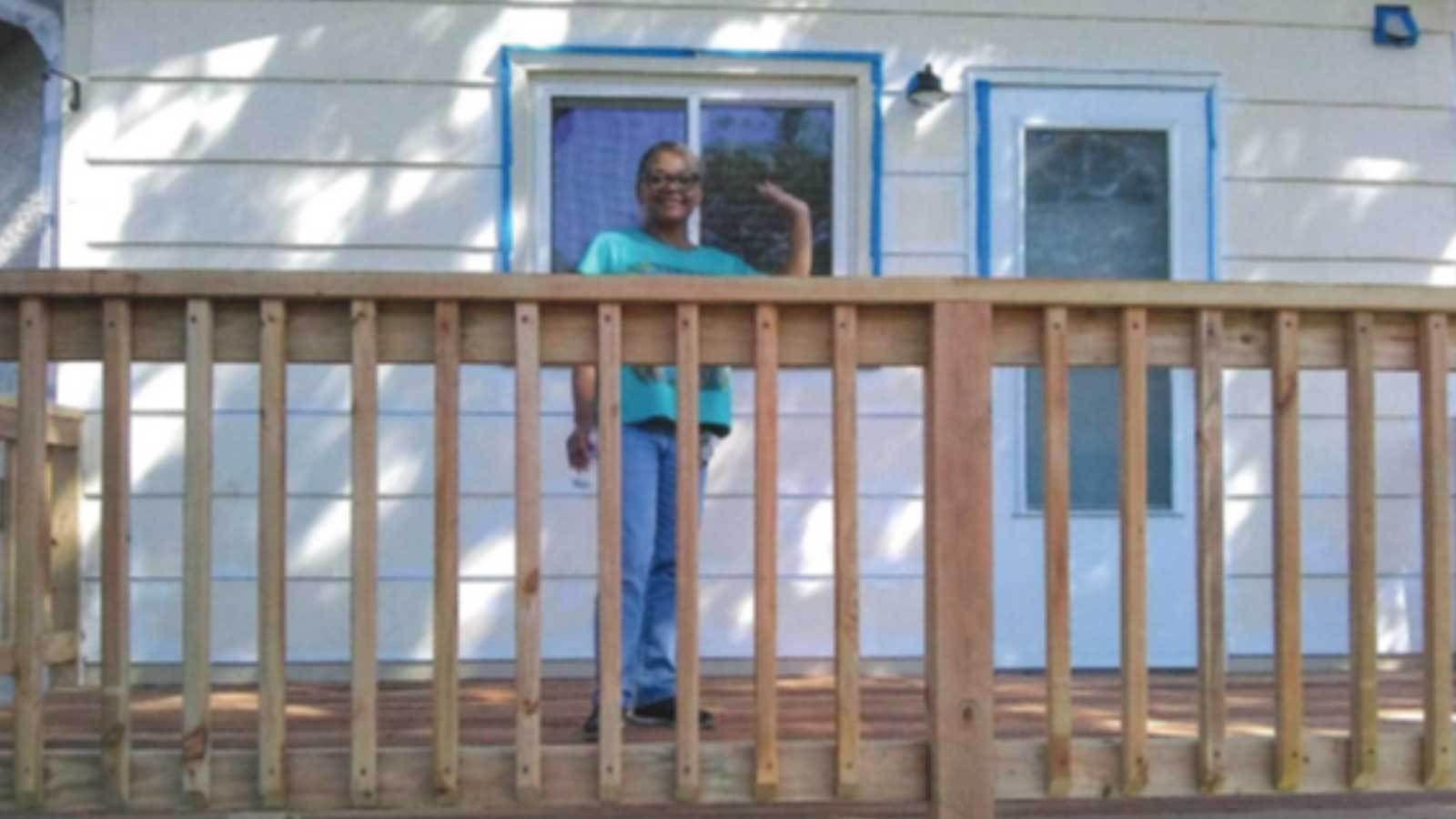 Nevonne standing on her new deck in a blue shirt and jeans, smiling and waving.